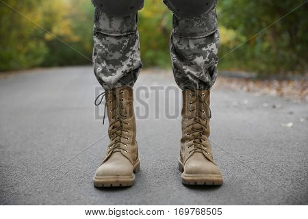 Feet of soldier standing on asphalt road, close up view