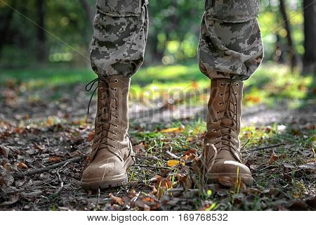 Feet of soldier standing in forest, close up view