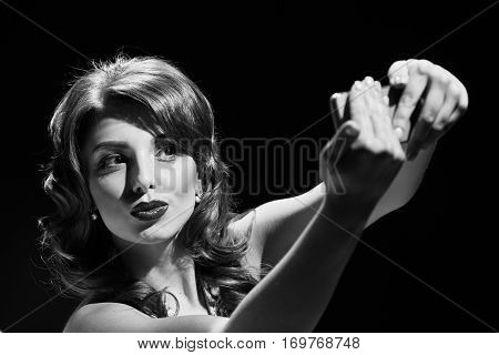 woman in dress studio portrait in hollywood style light on black background. making selfie. in black and white toning