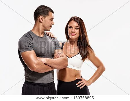 Beautiful athletic muscular couple in sportswear on white