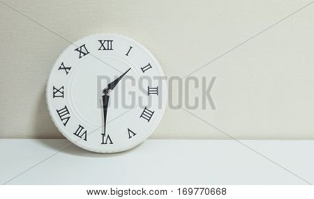 Closeup white clock for decorate show half past one p.m. or 1:30 p.m. on white wood desk and cream wallpaper textured background with copy space