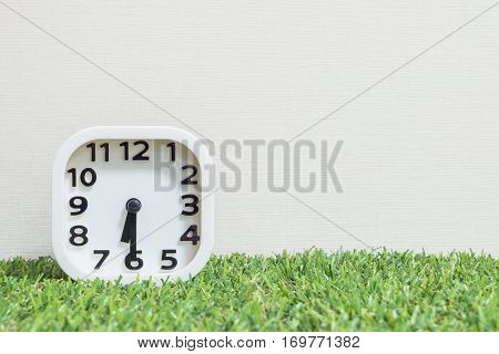 Closeup white clock for decorate show a half past six or 6:30 a.m. on green artificial grass floor and cream wallpaper textured background with copy space
