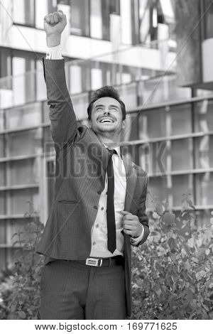 Excited businessman celebrating success outside office building