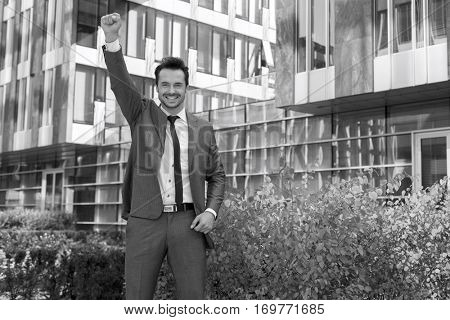 Portrait of successful businessman with arm raised standing outside office building