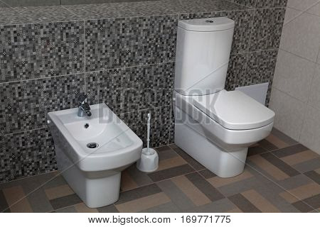 white toilet and bidet in a modern bathroom