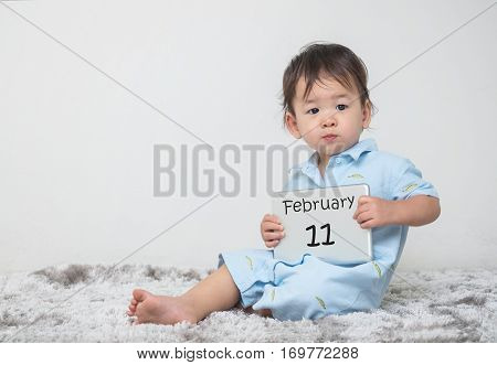 Closeup cute asian kid show calendar on plate in his hand in february 11 word on gray carpet and white cement wall textured background with copy space