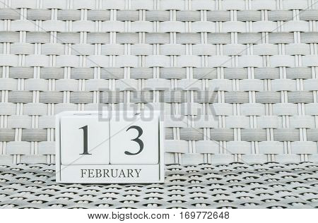 Closeup surface white wooden calendar with black 13 february word on blurred weave wood chair textured background with copy space in selective focus at the calendar