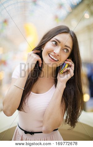 Young beautiful brunette woman in pink dress calling on a cell phone, posing against a background of a New Years interior