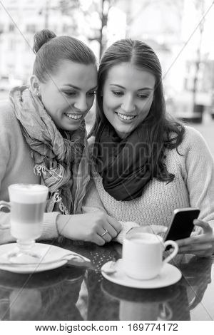 Happy women using cell phone at sidewalk cafe