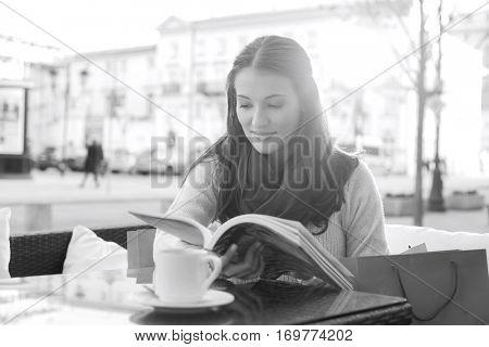 Beautiful woman reading book at sidewalk cafe