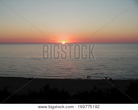 Sunset on Lake Michigan with silouettes at the shore