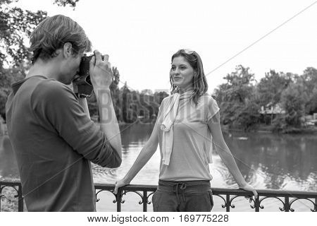 Young man photographing woman at lakeside