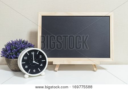 Closeup alarm clock for decorate show 4 o'clock with wood black board on white wood desk and cream wallpaper textured background selective focus at the clock