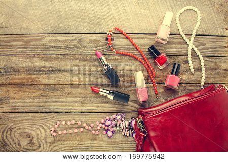 Women's accessories: cosmetic bag, necklace, nail polish, lipstick. Top view. Toned image.