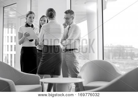 Business people discussing over documents in lobby
