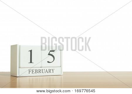 Closeup surface white wooden calendar with black 15 february word on blurred brown wood desk isolated on white background with copy space selective focus at the calendar