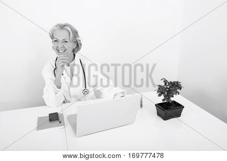 Happy senior female doctor with laptop at desk in clinic
