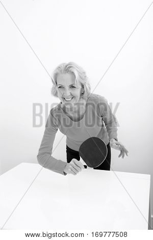 Happy senior woman playing table tennis