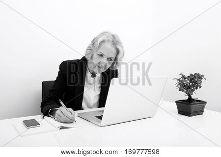 Senior businesswoman writing in book while using laptop at desk in office