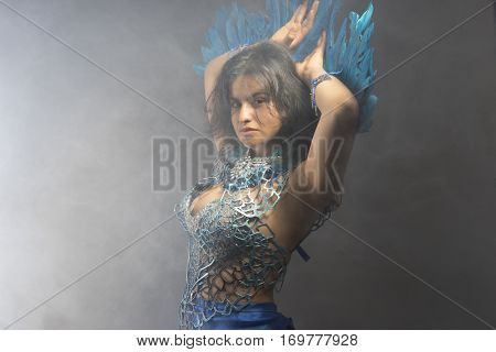 Glamour, Brunette woman in costume made of blue feathers, wild and free bird, fantasy image