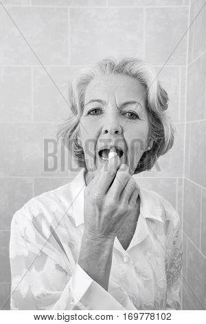 Portrait of senior woman applying lipstick in bathroom