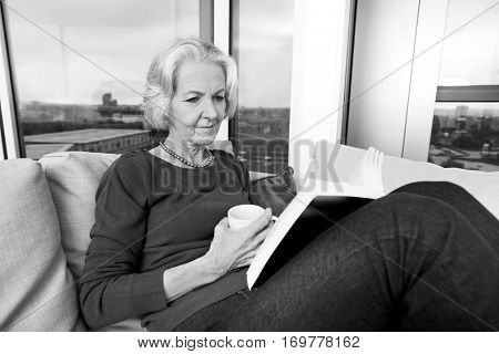 Senior woman reading book on sofa at home
