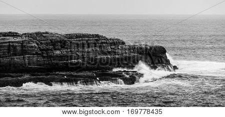 Ocean Waves Breaking On Rugged Coastal Cliffs. Black And White Landscape.
