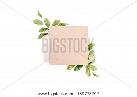 Craft gift box and floral composition with green leaves on white background. Flat lay top view.