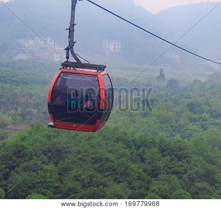Photo of Cable Car on Green Epic Scenery Background. Cable Cabin on Ropeway on Green Landscape