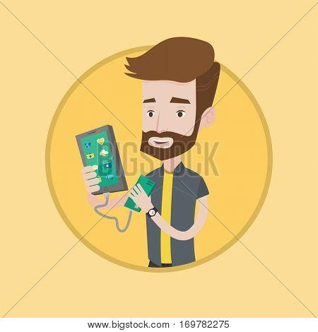 Hipster man recharging his smartphone with mobile phone portable battery. Young man holding a mobile phone and battery power bank. Vector flat design illustration in the circle isolated on background.
