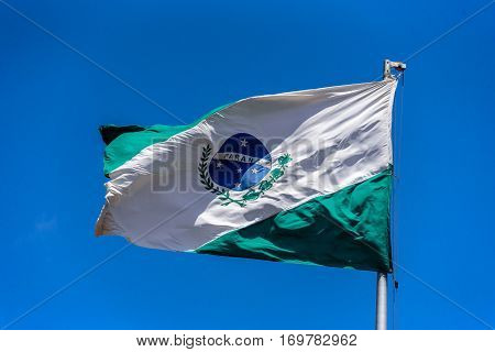 Flag of Parana waving in the wind at flagpole on the background of clear blue sky at sunny summer day, Brazil