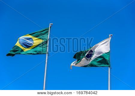 National brazilian flag and flag of Parana waving in the wind at flagpoles on the background of clear blue sky at sunny summer day, Brazil