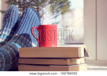 red mug on a pile of books on background feet in warm socks on a table next to the window / warming atmosphere holiday home
