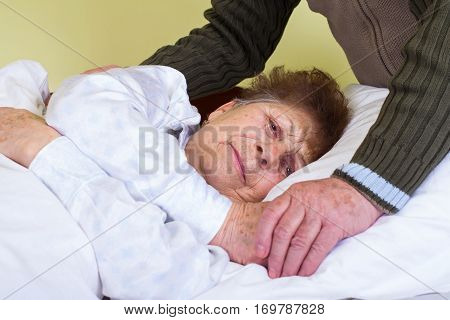 Close up picture of an invalid woman with her husband's hands