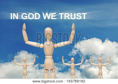 Wooden dummy puppet on sky background with words IN GOD WE TRUST. Abstract conceptual image