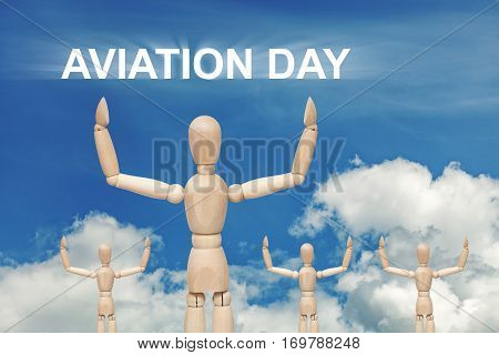 Wooden dummy puppet on sky background with words AVIATION DAY. Abstract conceptual image