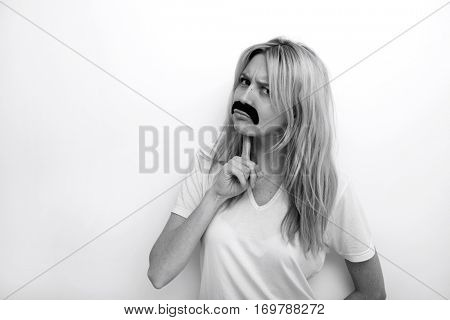 Portrait of confused in fake mustache against white background