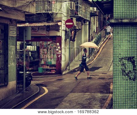 Macao - October 2016: Man with umbrella walking in small street.