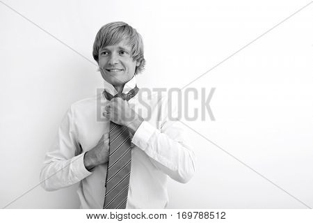 Portrait of mid adult businessman tying tie against white background