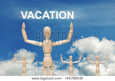 Wooden dummy puppet on sky background with word VACATION. Abstract conceptual image