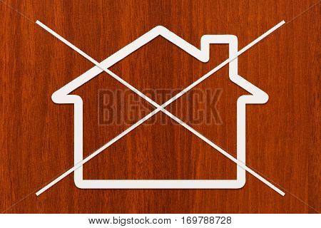 Strikethrough paper house on wooden background. Abstract conceptual image