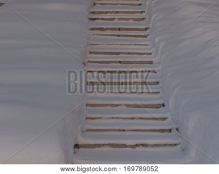 Stone steps leading on top between snowdrifts