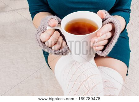Black tea in the hands of a young girl in a green dress. Fingerless gloves gray put on by on the hands of women