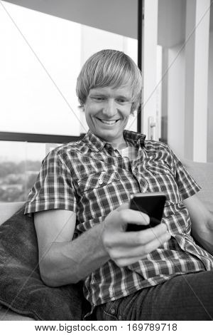 Smiling mid-adult man text messaging on sofa at home
