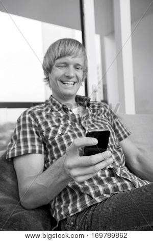 Cheerful mid-adult man text messaging on sofa at home