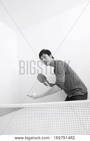 Mid adult man preparing to serve table tennis ball