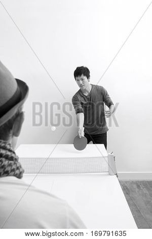 Mid adult man playing table tennis with friend