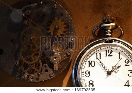 Time concept. Pocket watch near old clock mechanism