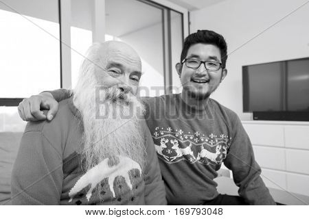 Portrait of grandson and grandfather smiling in house