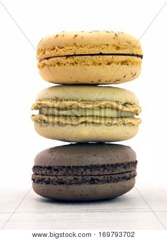 Three macaroons taken with a white wood background